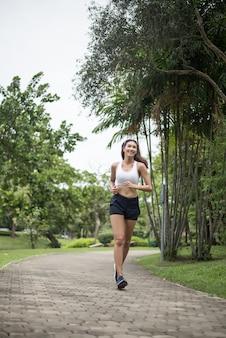 Jonge mooie sportvrouw die bij het park loopt. gezondheid en sport concept.