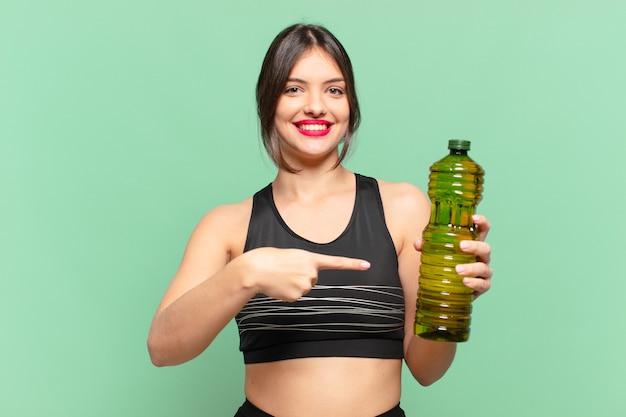 Jonge mooie sportvrouw die een oliefles aanwijst of toont en vasthoudt