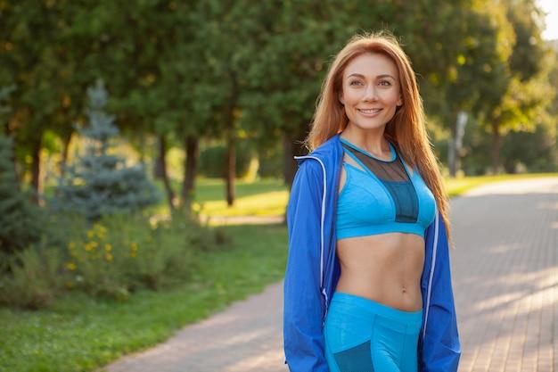 Jonge mooie sportvrouw die in het park loopt