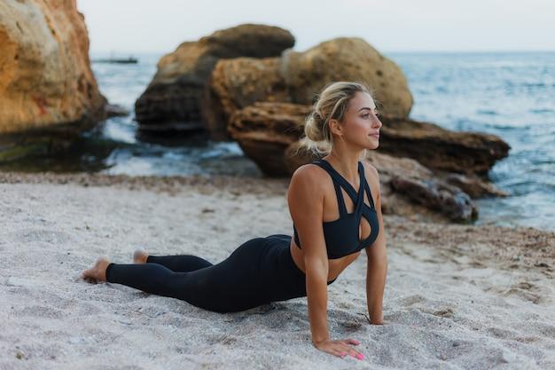 Jonge mooie sportvrouw die in sportkleding asanaoefening op het zand bij het wilde strand uitoefenen. outdoor yoga training