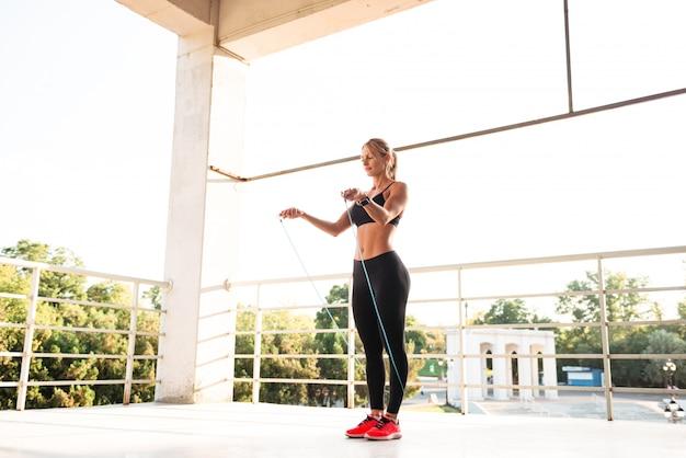 Jonge mooie sportvrouw die met touwtjespringen springt