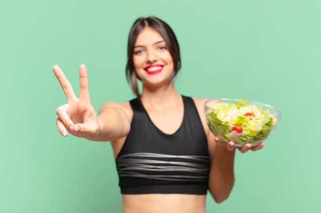 Jonge mooie sportvrouw die succesvol een overwinning viert en een salade houdt