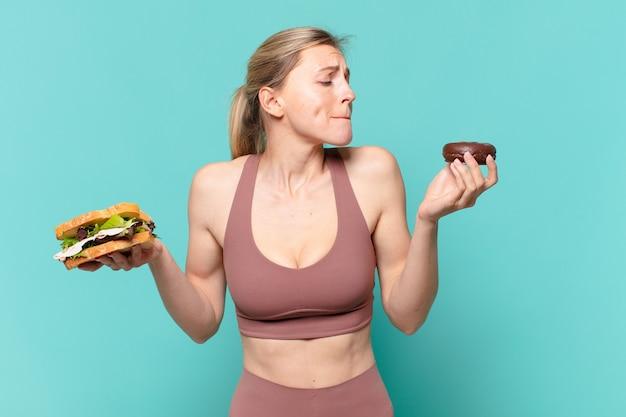 Jonge mooie sportvrouw die twijfelt of een onzekere uitdrukking heeft en een broodje en een donut vasthoudt