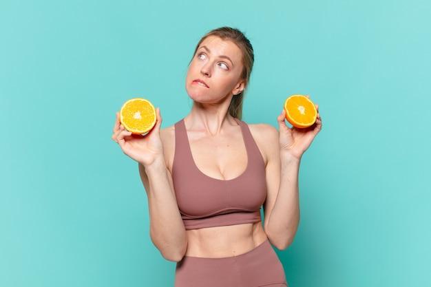 Jonge mooie sportvrouw die twijfelt of een onzekere uitdrukking heeft en een sinaasappel vasthoudt