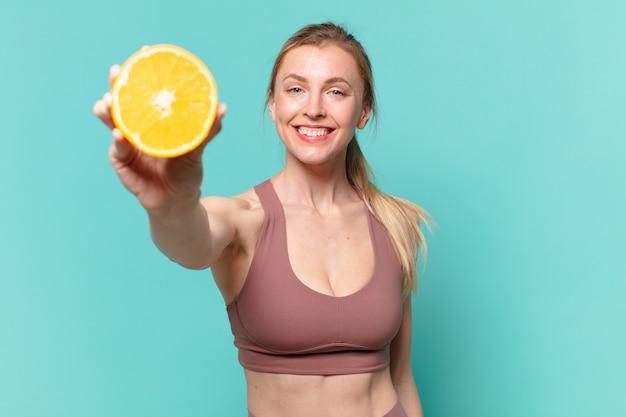 Jonge mooie sportvrouw gelukkige uitdrukking en houden een sinaasappel