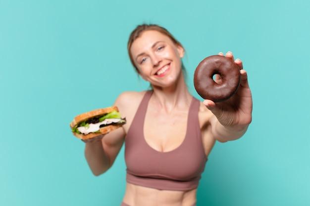 Jonge mooie sportvrouw gelukkige uitdrukking en met een broodje en een donut
