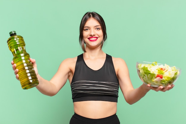 Jonge mooie sportvrouw gelukkige uitdrukking en met een salade