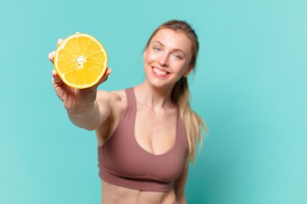 Jonge mooie sportvrouw gelukkige uitdrukking en met een sinaasappel