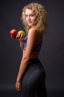 Jonge mooie sportvrouw klaar voor gymnastiek die gezonde appel houdt