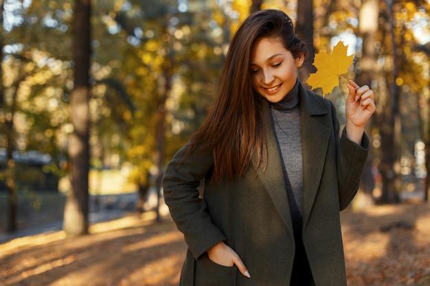 Jonge mooie stijlvolle gelukkig meisje met glimlach in een modieuze jas met een gouden herfstblad wandelingen in het park op een zonnige dag