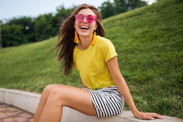 Jonge mooie stijlvolle lachende vrouw met plezier in stadspark, positief, emotioneel, gele top, gestreepte minirok, roze zonnebril, zomer stijl modetrend, lang haar, kleurrijk dragen