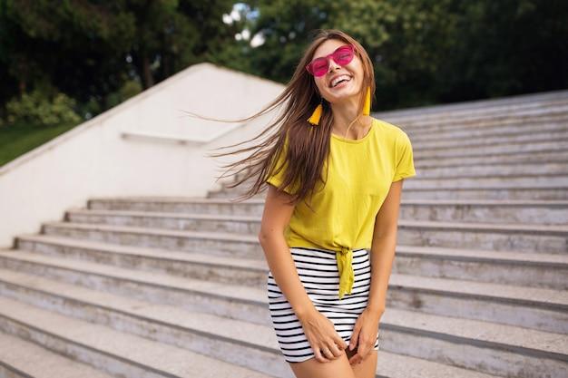 Jonge mooie stijlvolle lachende vrouw met plezier in stadspark, positief, emotioneel, gele top, gestreepte minirok, roze zonnebril, zomer stijl modetrend, positieve emotie dragen