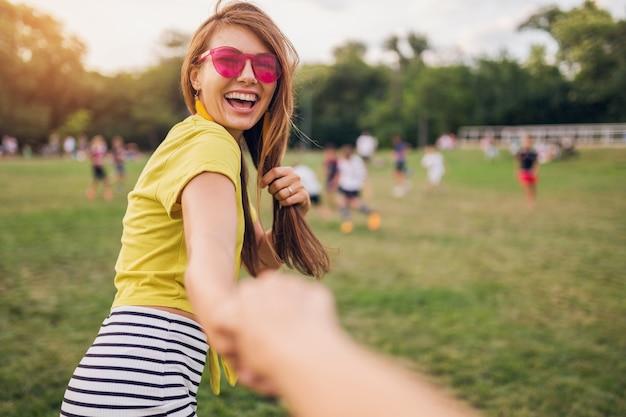 Jonge mooie stijlvolle lachende vrouw plezier in stadspark, hand van vriendje vasthouden, volg mij, positieve emotionele, gele top, roze zonnebril, zomer stijl modetrend dragen
