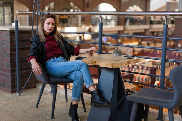 Jonge mooie stijlvolle moderne vrouw zitten aan een tafel in een café te wachten op vrienden na het winkelen. vrouw in lederen zwarte jas en spijkerbroek. jonge vrouw rusten indrukwekkend zit op een stoel.