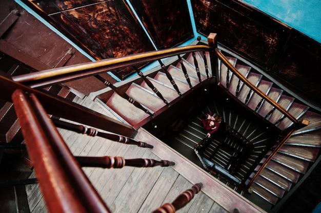 Jonge mooie stijlvolle paar in een rode jurk in grote houten vintage trappen