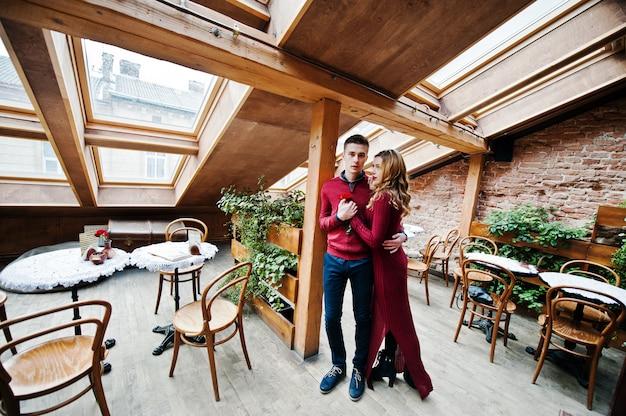 Jonge mooie stijlvolle paar in een rode jurk in liefdesverhaal in het vintage café met grote ramen op het dak