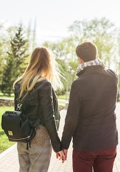 Jonge mooie stijlvolle paar verliefd hand in hand op straat, achteraanzicht