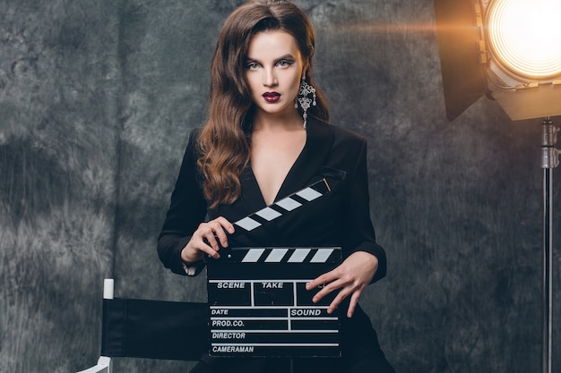 Jonge mooie stijlvolle sexy vrouw op bioscoop backstage, film klepel te houden