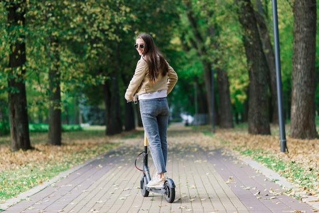 Jonge, mooie stijlvolle vrouw die op een elektrische scooter rijdt door het herfstpark, ecologisch transport