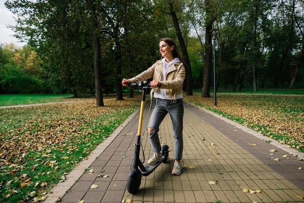 Jonge mooie stijlvolle vrouw elektrische scooter rijden door herfst park, ecologisch vervoer