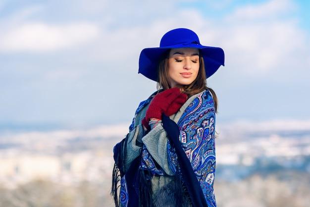 Jonge mooie stijlvolle vrouw in blauwe hoed en sjaal wandelen in het park
