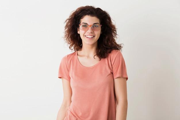 Jonge mooie stijlvolle vrouw in glazen, krullend haar, oprecht lachend, positieve emotie, gelukkig, geïsoleerd, roze t-shirt
