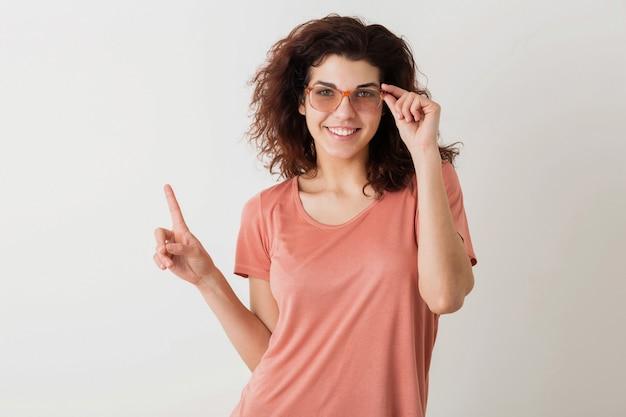 Jonge mooie stijlvolle vrouw in glazen met vinger, krullend haar, glimlachen, positieve stemming, gebaar, blij emotie, geïsoleerd, roze t-shirt