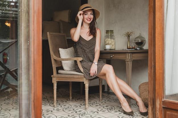 Jonge mooie stijlvolle vrouw in resort hotelkamer, zittend aan tafel, trendy jurk dragen, safari stijl, strooien hoed, glimlachen, gelukkig, zomervakantie, boheemse outfit