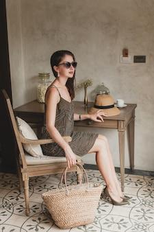 Jonge mooie stijlvolle vrouw in resort hotelkamer, zittend aan tafel, trendy jurk dragen, safaristijl, strooien hoed, glimlachen, gelukkig, zomervakantie, boheemse outfit, strandtas, zonnebril, benen