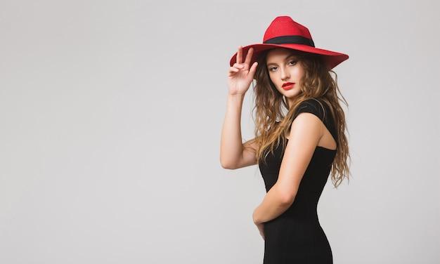 Jonge mooie stijlvolle vrouw in zwarte jurk, rode hoed, rode lippenstift, gelukkig, glimlachen, sexy, elegant