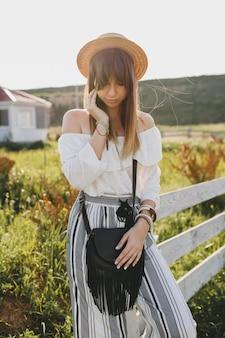 Jonge mooie stijlvolle vrouw lente zomer modetrend, boho stijl, strooien hoed, platteland weekend, zonnige, zwarte tas