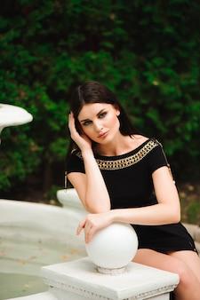 Jonge mooie stijlvolle vrouw lopen en poseren in korte zwarte jurk in de stad in de buurt van fonteinen. outdoor zomer portret van jonge stijlvolle vrouw.