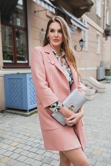 Jonge mooie stijlvolle vrouw lopen in de straat in roze jas, portemonnee in handen houden, luisteren naar muziek