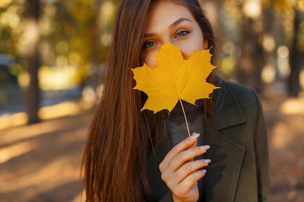 Jonge mooie stijlvolle vrouw met blauwe ogen in een modieuze jas, met een geel herfstblad in de buurt van het gezicht tijdens het wandelen in het park. de herfstportret van de close-up van gelukkig meisje
