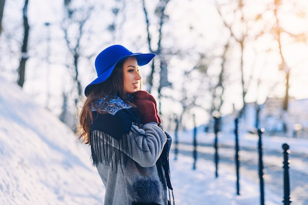 Jonge mooie stijlvolle vrouw met perfecte glimlach in blauwe hoed en sjaal die onderaan de straat loopt