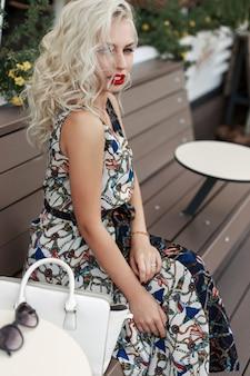 Jonge mooie stijlvolle vrouw met rode lippen met een kapsel in een modieuze jurk met een patroon met een witte tas en zonnebril zit op een houten bankje in de stad