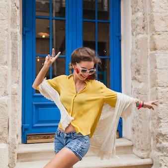 Jonge mooie stijlvolle vrouw wandelen in de oude stad straat