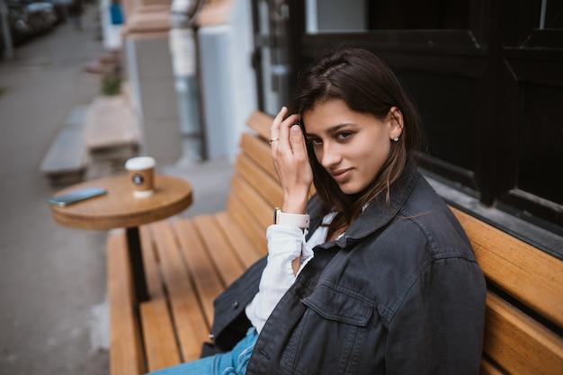 Jonge mooie stijlvolle vrouw, zittend op de straat bankje