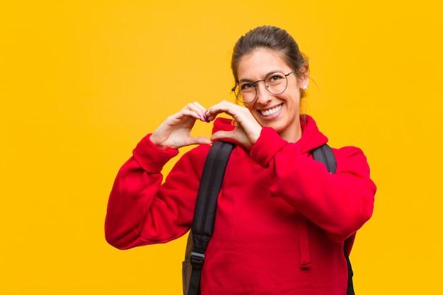 Jonge mooie student die en gelukkig, leuk, romantisch en in liefde glimlacht voelt, die hartvorm met beide handen maakt