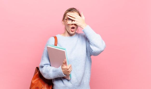 Jonge mooie student die geschokt, bang of doodsbang kijkt, het gezicht bedekt met de hand en tussen de vingers gluurt