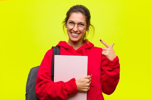 Jonge mooie student die of eigen glimlach met beide handen ontwerpen schetsen, die positief en gelukkig, wellnessconcept kijken