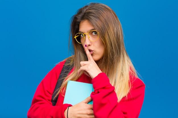 Jonge mooie student die om stilte en stil vraagt, gebaren met vinger voor mond, shh zegt of een geheim bewaart