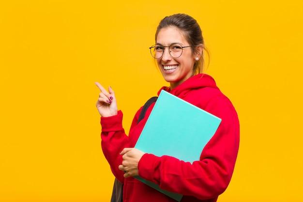 Jonge mooie student die vrolijk gelukkig het voelen glimlachen en aan de kant en naar omhoog tonend voorwerp in exemplaarruimte glimlachen