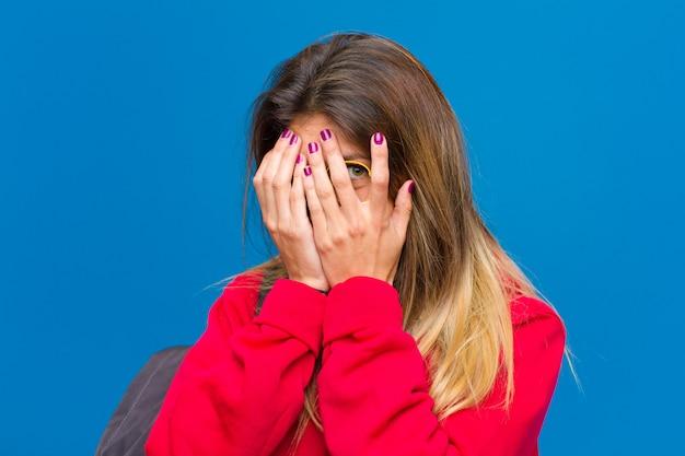 Jonge mooie student die zich bang voelt, gluurt of spioneert met ogen half bedekt met handen