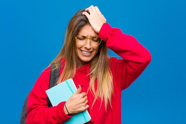 Jonge mooie student die zich gestrest en angstig, depressief en gefrustreerd voelt met hoofdpijn en beide handen opheft