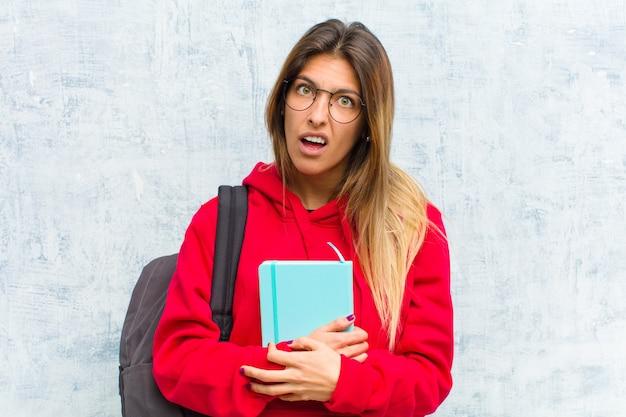 Jonge mooie student die zich verbaasd en verward voelt, met een domme, verbijsterde uitdrukking die naar iets onverwachts kijkt