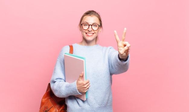 Jonge mooie student lacht en ziet er gelukkig, zorgeloos en positief uit, gebarend overwinning of vrede met één hand