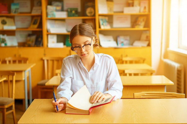Jonge mooie student met een bril zitten aan een tafel in het kantoor en het lezen van een boek.