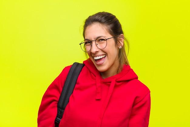 Jonge mooie student met een grote, vriendelijke, zorgeloze glimlach, die er positief, ontspannen en gelukkig uitziet, chillen
