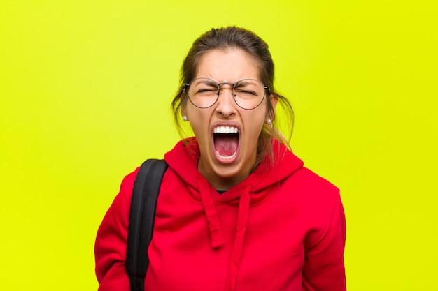 Jonge mooie student schreeuwt agressief, ziet er heel boos, gefrustreerd, verontwaardigd of geïrriteerd uit, schreeuwt nee